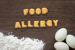 Letter biscuits word FOOD ALLERGY on kitchen table background Stock Photos
