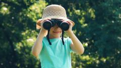Girl is naturalist explorer looking through binoculars at camera and laughing - stock footage