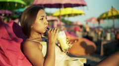 Pretty, young woman drinking cocktail while sitting on pouf on beach HD Stock Footage