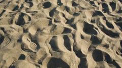 Foot prints in sandy beach, tilting up sand to ocean, people looking at water Stock Footage