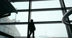 Child by the window and woman with suitcase Stock Footage
