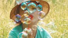Closeup portrait girl blowing soap bubbles in the grass and smiling at camera Stock Footage