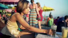 Woman finishing working on laptop drinking cocktail sitting on pouf on bech HD Stock Footage