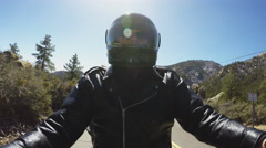 Backlit Helmeted Motorcycle Rider On Mountain Highway Stock Footage