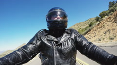 Low Angle Motorcycle Rider On Curving Desert Highway Stock Footage