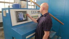 Man programing a cubic-presser at synthetic diamonds factory - stock footage