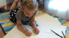 Little girl is drawing on floor Stock Footage