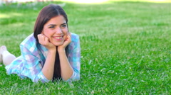 Girl relaxing outdoors looking happy and smiling Stock Footage