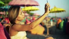 Young woman drinking cocktail and taking selfie photo with cellphone on pouf  HD Stock Footage