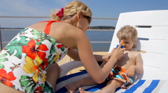 Young mother using sun skin cream protection to her baby sunbathing in chair Stock Footage