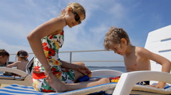 Young woman applying sun block on the legs of little boy Stock Footage
