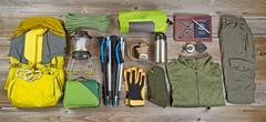 Hiking and camping gear organized on rustic wooden boards Stock Photos