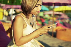 Pretty, young woman using smartphone while sitting on pouf on beach NTSC Stock Footage