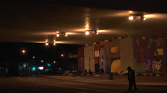 Homeless people living under a bridge at night in the city Stock Footage