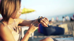 Young woman with smartwatch sitting on pouf on beach HD Stock Footage