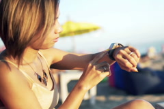 Young woman with smartwatch sitting on pouf on beach NTSC Stock Footage