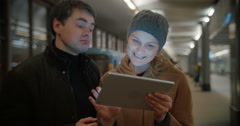 Young people discussing something using pad at metro station Stock Footage