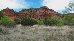 Grassy Valley Floor And Rocky Ridge- Caprock Canyon State Park Stock Footage