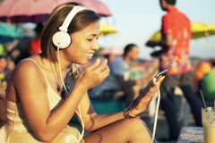 Young woman watching movie on tablet computer sitting on pouf on beach NTSC Stock Footage