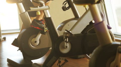 Young man working out on the exercise bike in the fitness center - stock footage