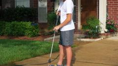 Teenage boy powerwashing a dirty driveway Stock Footage