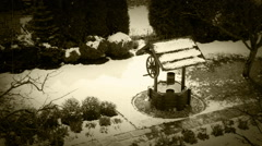 Backyard garden scene: snow falling on the ground and a vintage well Stock Footage