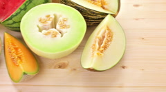 Variety of organic melons sliced on wood table. Stock Footage