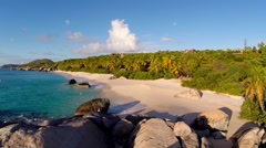 Aerial drone pull-away shot over white sand beach with bolders in the BVI Stock Footage