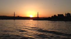 Sunset with a ferry at The Golden Horn with the Atatürk Bridge in Istanbul Stock Footage