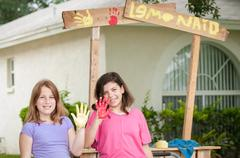 Two young girls painting a lemonade stand sign Stock Photos