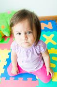 Adorable baby girl sitting on knees - stock photo