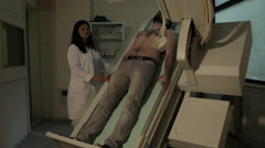 Female doctor radiologist examining male patient with scanner on radiology ward. - stock footage