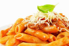 Penne pasta with meat-based tomato sauce and cheese - stock photo