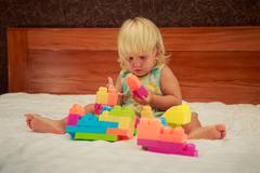 Little girl in pink looks with interest at toy constructor Stock Photos
