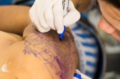 Tattoo artist drawing - stock photo