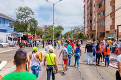 Multiple spectators street waking away from the Carnival parade colorful vendors - stock photo