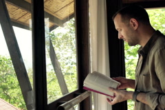 Young man reading book standing by window NTSC Stock Footage
