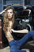 Tempting woman in garage with suitcase - stock photo