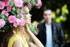 Passionate woman and man near rose bush Stock Photos