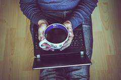 Young student with a cup of tea using a laptop and sitting on the wooden floor Stock Photos