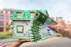 Real estate agent holding model house from paper - stock photo