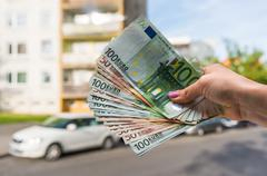 Property buyer holding euro banknotes and buying beautiful flat Stock Photos