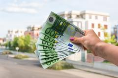 Property buyer holding euro banknotes and buying beautiful house Stock Photos