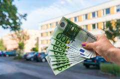 Property buyer holding euro banknotes and buying beautiful flat from real est - stock photo