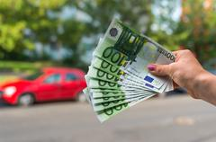 Car buyer holding euro banknotes and buying a new car from salesman on blurre Stock Photos