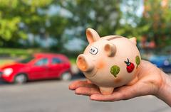 All savings money from pink ceramic piggy bank to pay for the dream car - stock photo