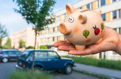 All savings money from pink ceramic piggy bank to pay for the dream home Stock Photos