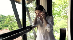 Sad woman getting bad news on cellphone standing by window HD Stock Footage