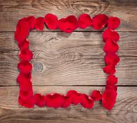 Design element. Frame of rose petals on the old boards - stock photo