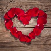 Heart of rose petals on the old wooden boards - stock photo